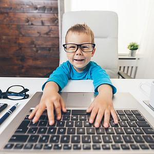 Dítě s brýlemi u počítače - optika Fénix Kroměříž